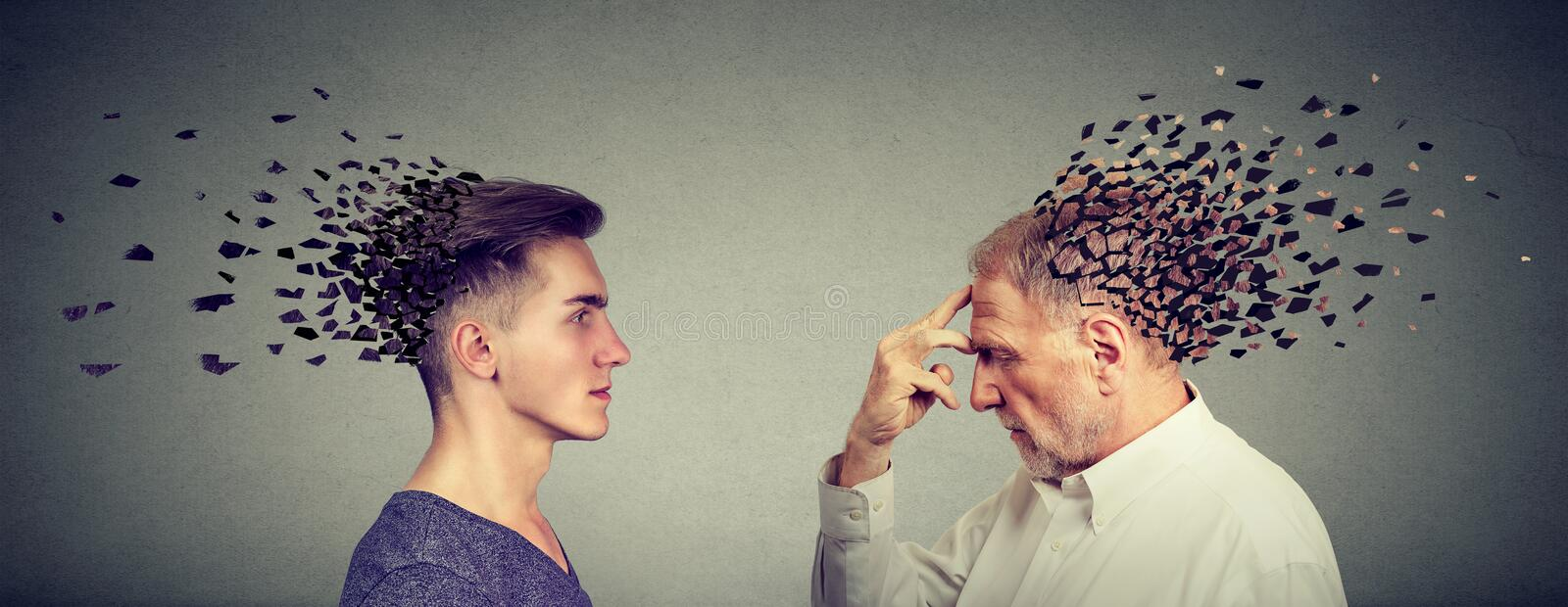 Memory loss due to dementia or brain damage. Side profile of young and senior men losing parts of head as symbol of decreased mind function royalty free stock image