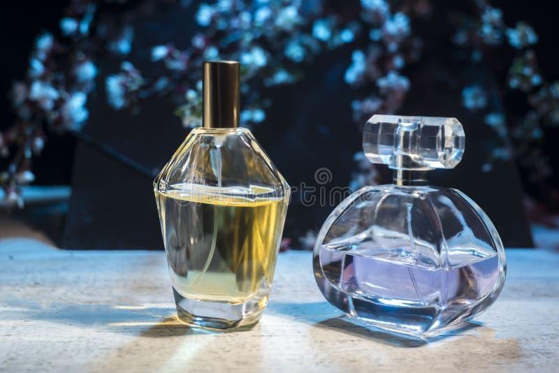 Men's i women's pachnidła w szklanej butelce na drewnianym stole przeciw tłu wiosna kwitniemy zdjęcie royalty free