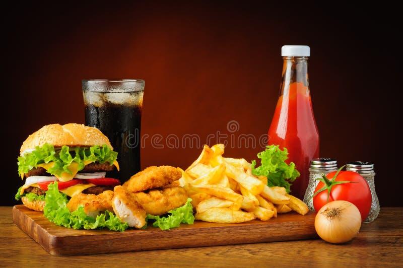 Menú de los alimentos de preparación rápida con la hamburguesa, las pepitas de pollo y las patatas fritas imagen de archivo libre de regalías