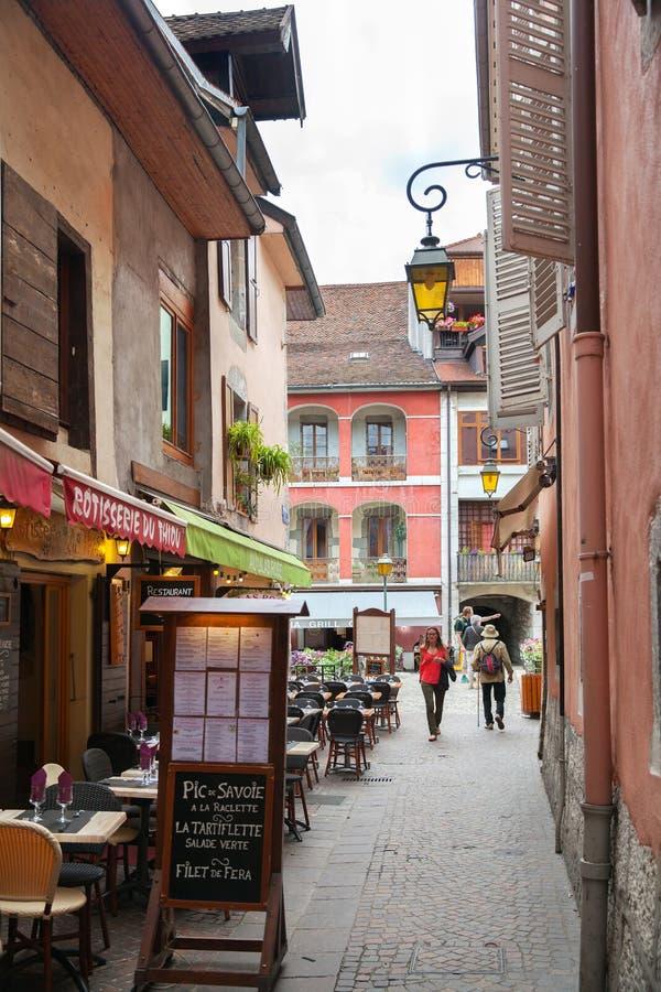 Menú y tablas en la calle estrecha entre casas coloridas típicas imagen de archivo