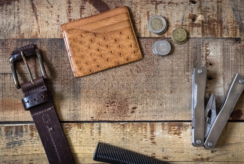 Men accessories. With belt, pocket knife, comb, card wallet and coins on wooden background stock images