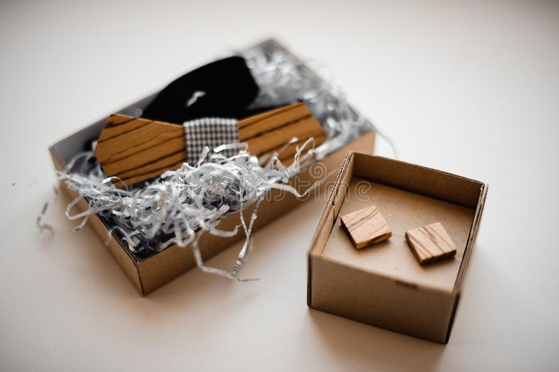 Men accessories. Elegant and stylish wooden bow tie and cufflinks arranged in a carton boxes. On the white background royalty free stock photo