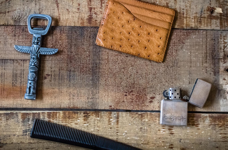 Men accessories. With lighter, bottle opener, comb and card wallet on wooden background stock image