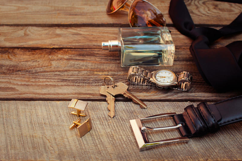 Men accessories. Sunglasses, bag, money, wrist watch, cufflinks, comb, strap, keys, perfume on the old wood background. Toned image stock images