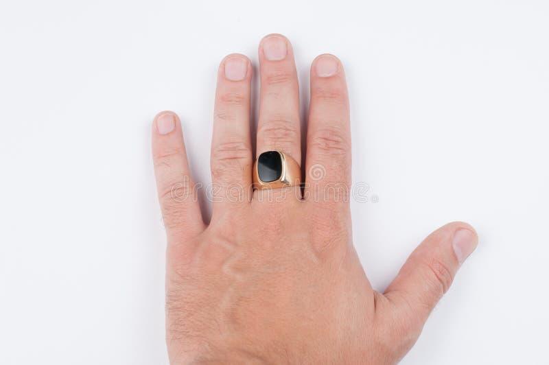 Men' anel dourado de s em sua mão isolada em um fundo branco imagens de stock