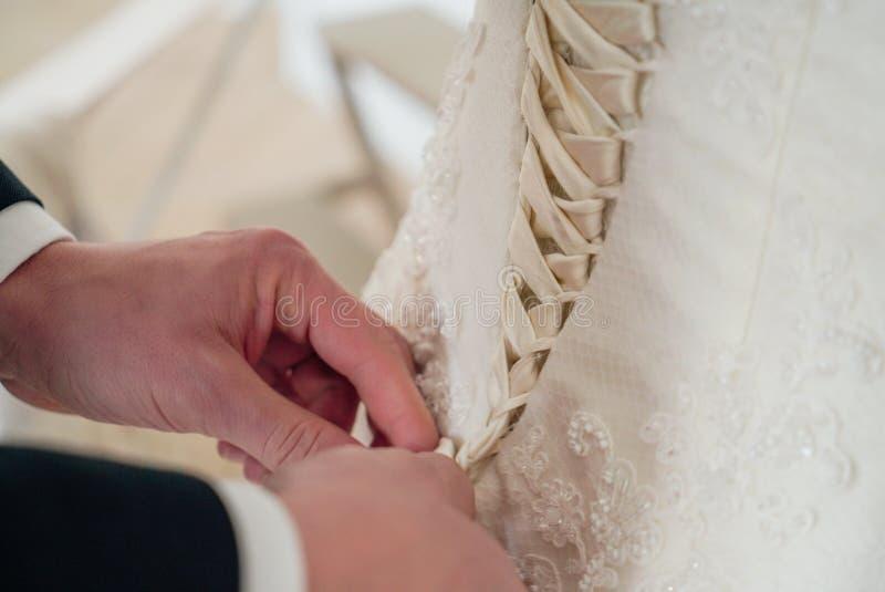 Men& x27; as mãos de s atam acima o espartilho no bride& x27; vestido de s, fim acima imagem de stock royalty free