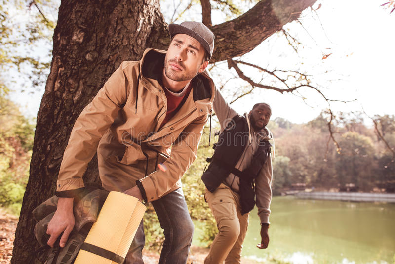 Men backpackers standing near river royalty free stock photos