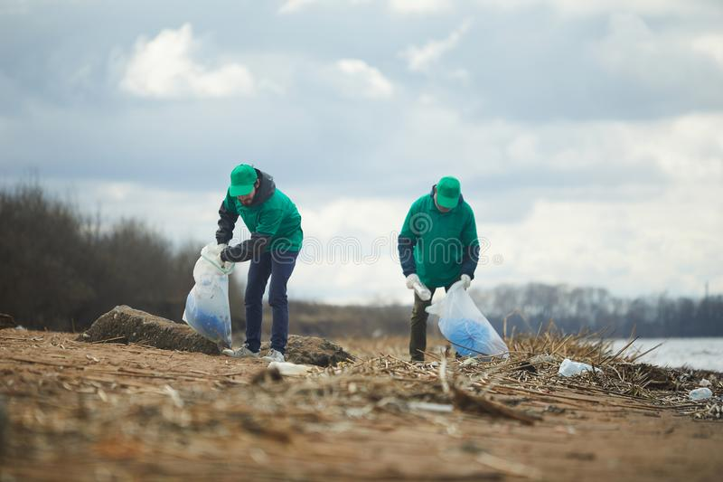 Men with bags collecting garbage. Two volunteers men in green uniform standing and collecting garbage on shore royalty free stock image