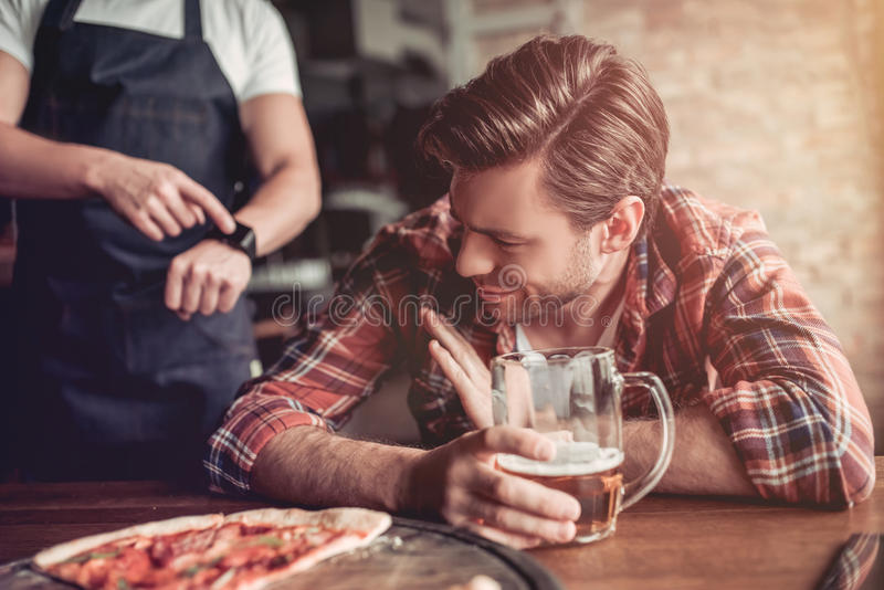 Men in bar. We are closed! Waiter is trying to get awake drunk visitor in bar royalty free stock photography
