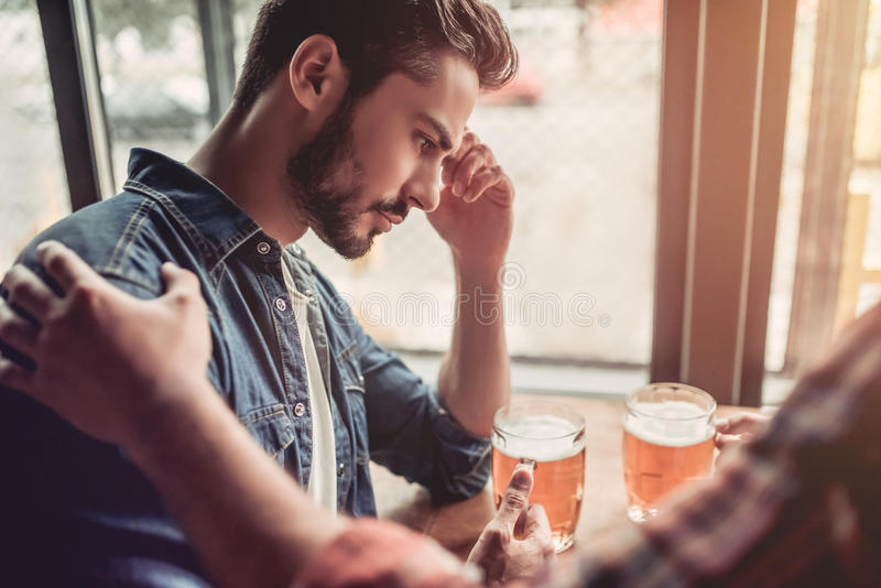Men in bar. Upset men in bar. Friend`s support royalty free stock photography