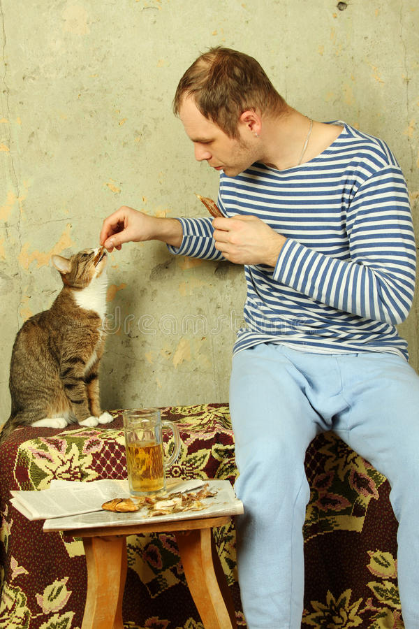 Download Men With A Beer Next To The Cat Steals Fish Stock Image - Image: 19243095