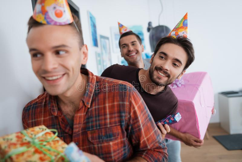 Men in birthday hats are preparing a surprise birthday party. They are preparing to meet the birthday girl. stock photo