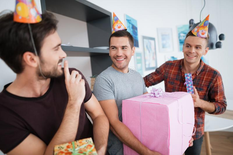 Men in birthday hats are preparing a surprise birthday party. They are preparing to meet the birthday girl. They are holding a presents in their hands royalty free stock image