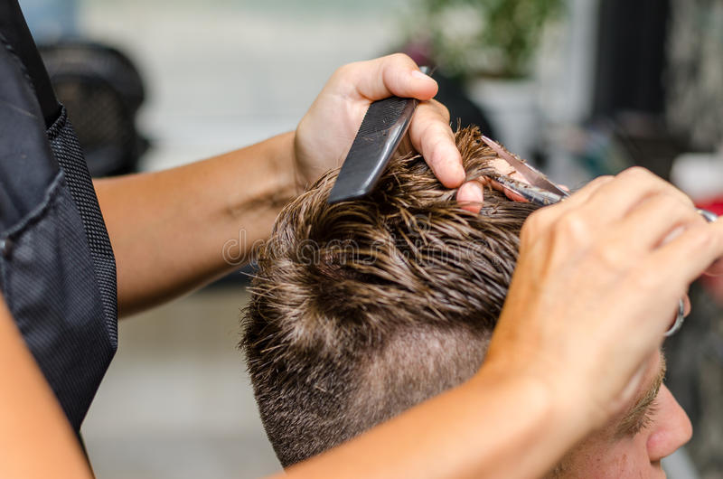 Men& x27; bitande sax för s-hår i en skönhetsalong royaltyfria foton