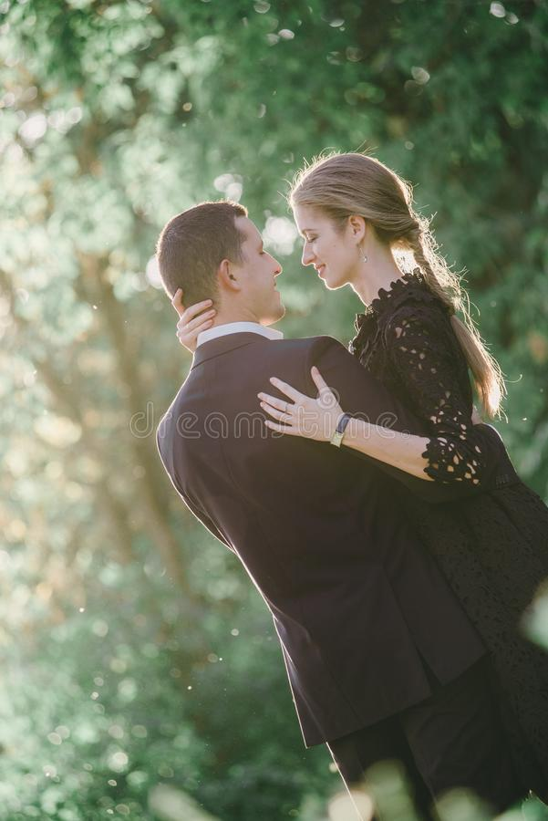 Man in black embracing his woman. A men in black embracing his woman, she is looking at him happily, isolated in green royalty free stock images