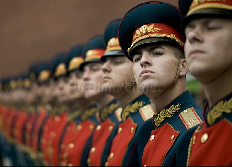 Men in Black and Red Cade Hats and Military Uniform stock image