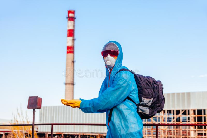 Man environmental mask face pack disguise facemask photo us Pisa tower protective overall blue pipeline plant factory disused. Men in blue protective overall at royalty free stock image