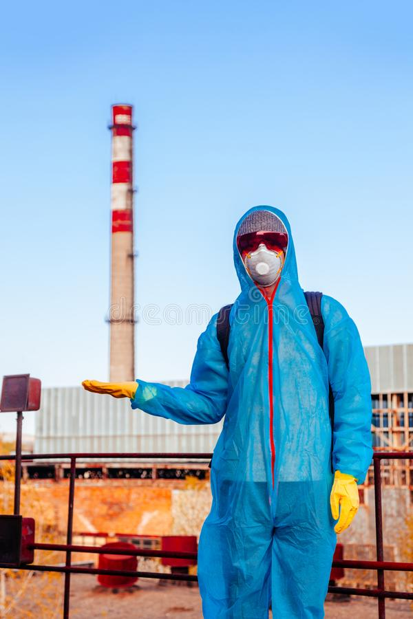Man environmental mask face pack disguise facemask photo us Pisa tower protective overall blue pipeline plant factory disused. Men in blue protective overall at stock photo