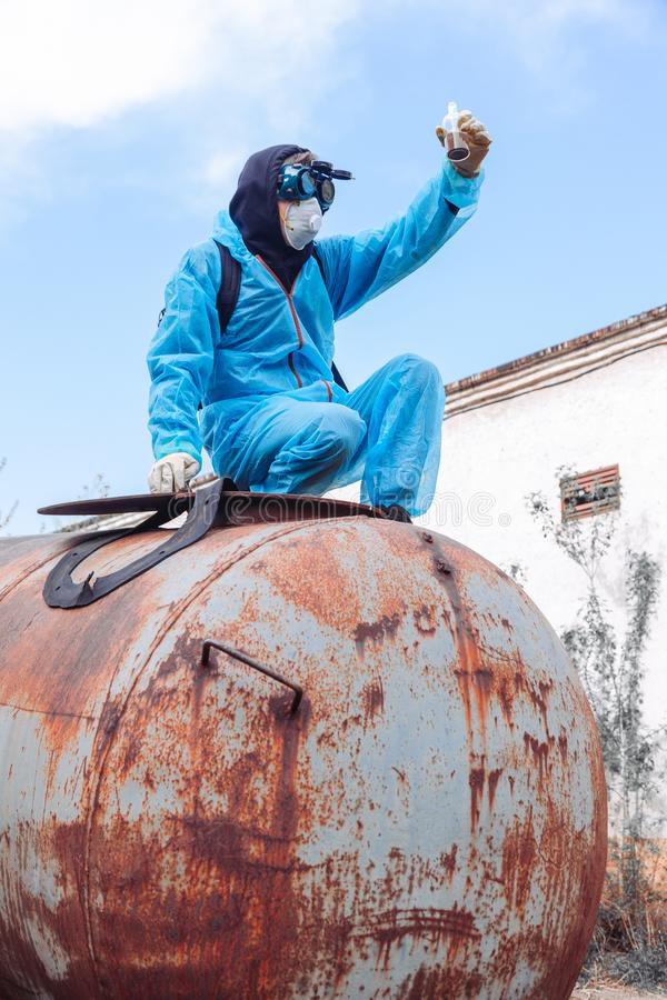 Man environment mask drum pack disguise facemask water muddy protective overall blue rast plant factory disused catastrophe. Men in blue protective overall at stock photo