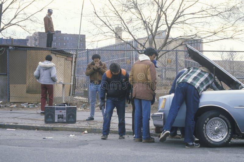 Men with boom box repairing car. South Bronx, New York stock photos