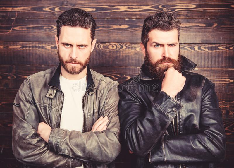 Men brutal bearded hipster posing in fashionable black leather jackets. Leather fashion menswear. Handsome stylish and royalty free stock photos