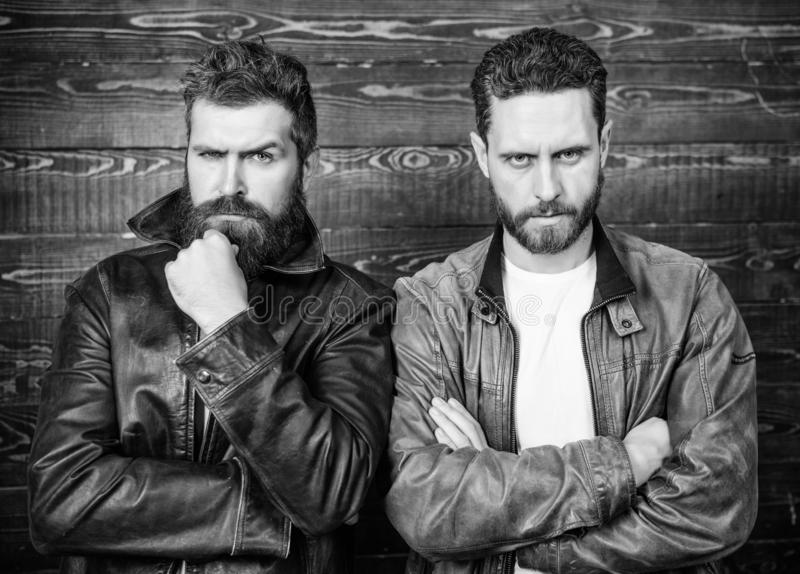 Men brutal bearded hipster posing in fashionable black leather jackets. Leather fashion menswear. Handsome stylish and royalty free stock photography