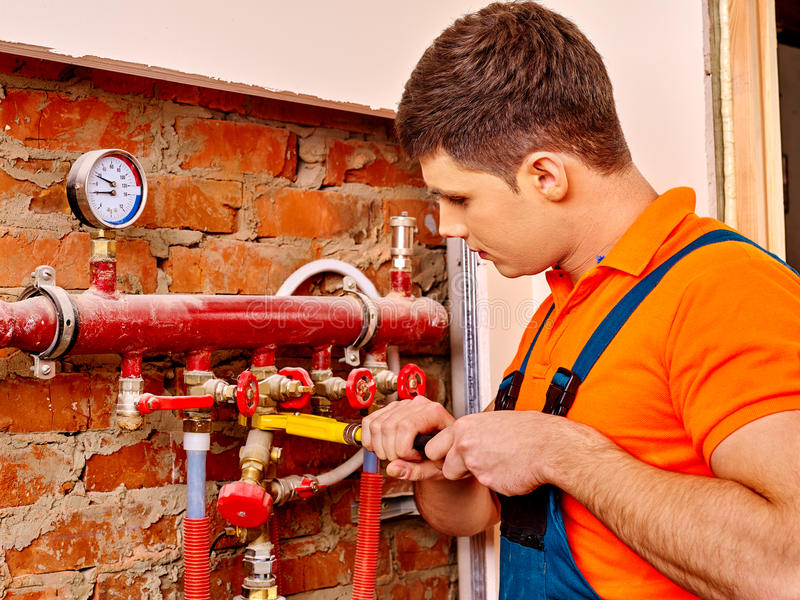 Men builder fixing heating system. With special tool royalty free stock image