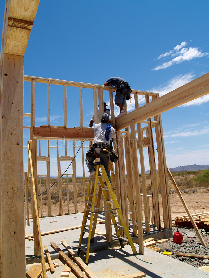 Men Building Frame for House - Vertical. Three men are working on building a wall of a house. They are looking at their work with their backs facing the camera royalty free stock photography
