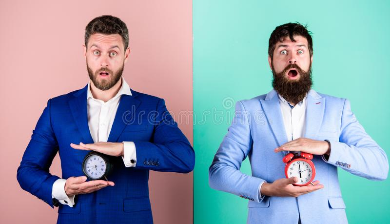 Men business formal suits hold alarm clocks. Lack of self discipline in time management leads people to procrastinate. Take control of your habits. Control and stock image