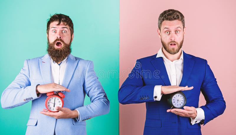 Men business formal suits hold alarm clocks. Lack of self discipline in time management leads people to procrastinate. Take control of your habits. Control and royalty free stock photo