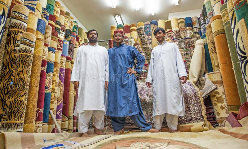 Men at the Carpet Souk in Abu Dhabi. ABU DHABI, UAE - FEBRUARY 23, 2006: A group of unidentified male Pakistani salesmen at the carpet souk in Abu Dhabi, the royalty free stock image