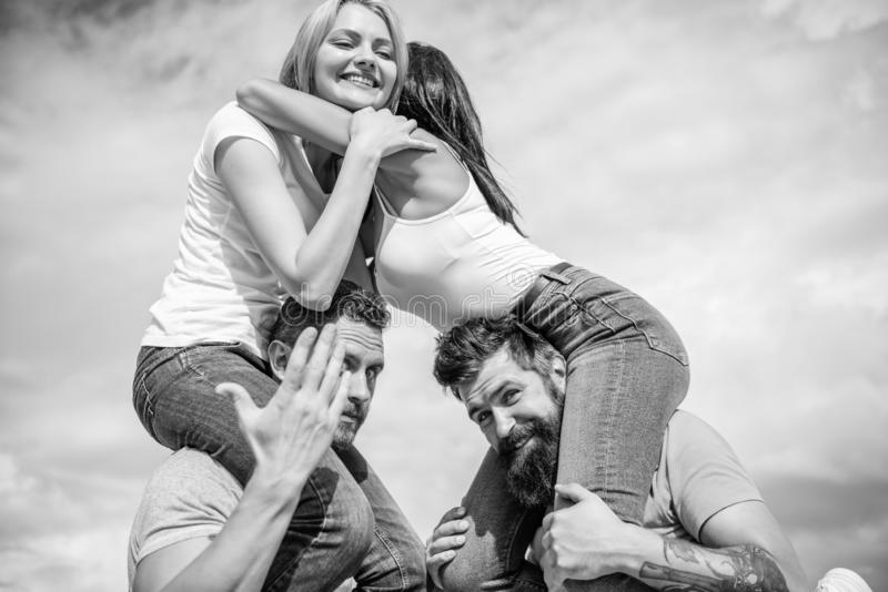 Men carry girlfriends on shoulders. Summer vacation and fun. Couples on double date. Inviting another couple to join. Friendship of families. Twice fun on stock photo