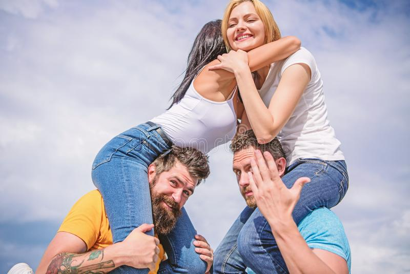 Men carry girlfriends on shoulders. Summer vacation and fun. Couples on double date. Inviting another couple to join. Friendship of families. Twice fun on royalty free stock photography