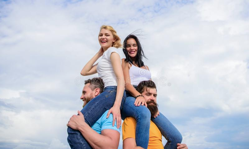 Men carry girlfriends on shoulders. Summer vacation and fun. Couples on double date. Inviting another couple to join. Twice fun on double date. Friendship of stock image