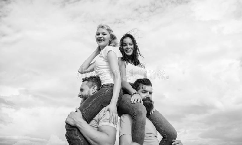 Men carry girlfriends on shoulders. Summer vacation and fun. Couples on double date. Inviting another couple to join. Twice fun on double date. Friendship of stock photography