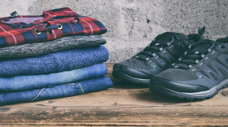 Men casual outfit. Men's shoes, clothing and accessories on wooden background - sweater, jeans, sneakers. Top view. Flat lay. Men casual outfit. The Men&# royalty free stock images