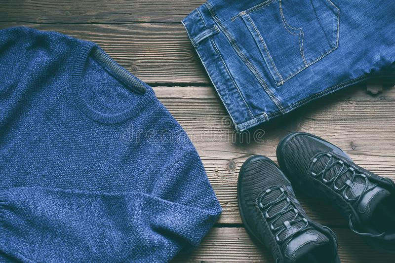 Men casual outfit. Men's shoes, clothing and accessories on wooden background - sweater, jeans, sneakers. Top view. Flat lay. The Men casual outfit. Men&# royalty free stock images