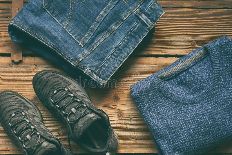Men casual outfit. Men's shoes, clothing and accessories on wooden background - sweater, jeans, sneakers. Top view. Flat lay. The Men casual outfit. Men&# stock photography