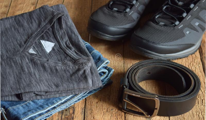 Men casual outfits. Men shoes, clothing and accessories on wooden background - grey t-shirt, blue jeans, sneakers, belt. Top vi stock photography