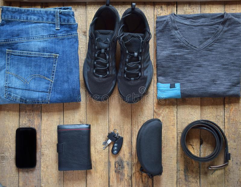 Men casual outfits. Men shoes, clothing and accessories on wooden background - grey t-shirt, blue jeans, sneakers with eyeglass. Es, wallet, belt. Top view. Flat stock photography