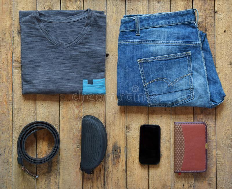 Men casual outfits. Men shoes, clothing and accessories on wooden background - grey t-shirt, blue jeans, sneakers with eyeglass. Es, wallet, belt. Top view. Flat stock images