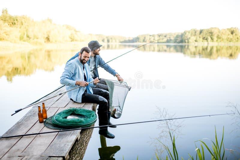 Men catching fish on the lake stock photos