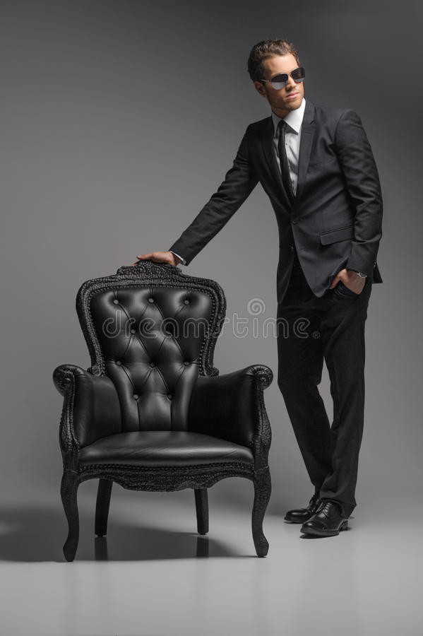 Men with chair. Full length of confident young businessmen in sunglasses standing near the vintage chair while isolated on grey royalty free stock photography