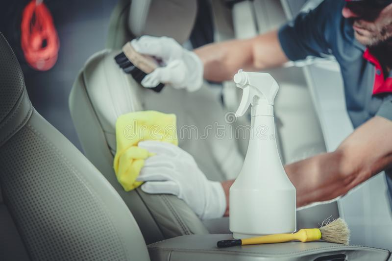 Men Cleaning Car Interior. Caucasian Men Cleaning Car Interior. Professional Detailed Vehicle Maintenance royalty free stock image