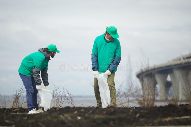 Men cleaning dirty shore royalty free stock photography