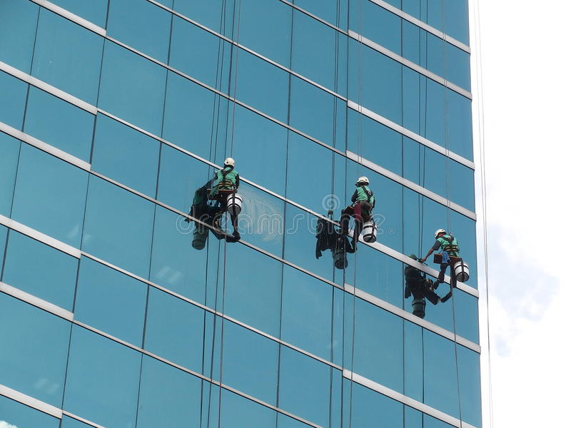 Men cleaning glass building by rope access at height royalty free stock photos