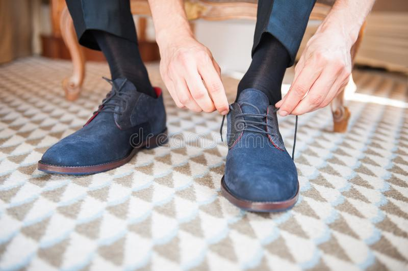 Men closing shoelace on blue suede shoes royalty free stock photography
