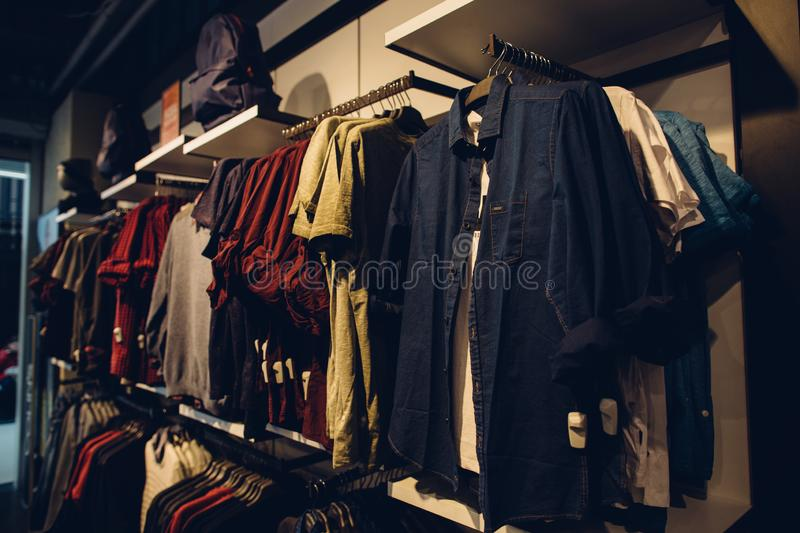Stylish men`s youth clothes in shopping clothes store. stock images