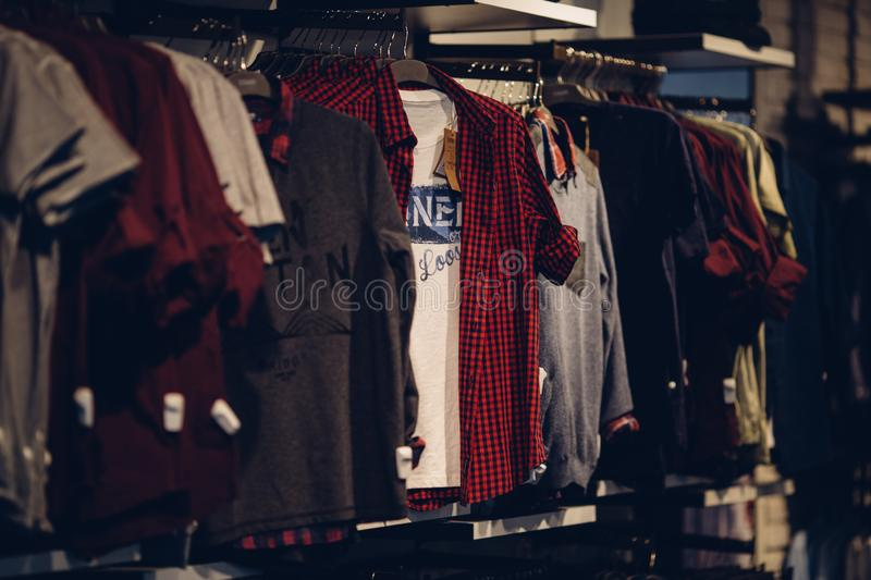 Youth men`s clothing on rack in clothes store royalty free stock photography