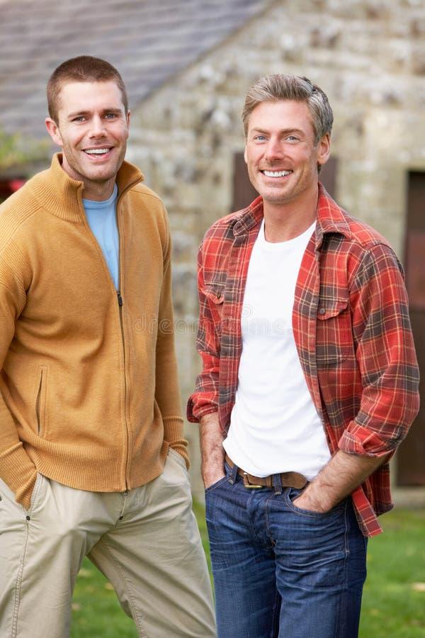 Men in country garden. Smiling royalty free stock photos